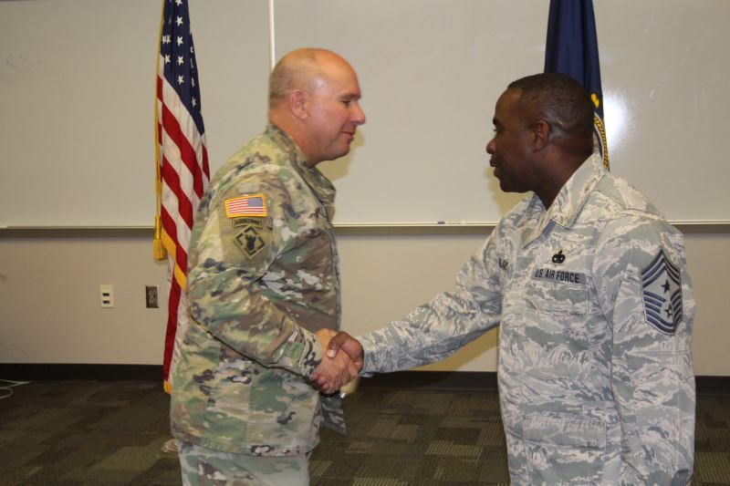 Maj. Gen. Lee Tafanelli congratulates Chommand Chief Master Sgt. Maurice Williams after he is sworn in as the state's new senior enlisted leader.